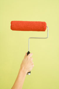 Caucasian female hand holding paint roller dipped in red against green wall.